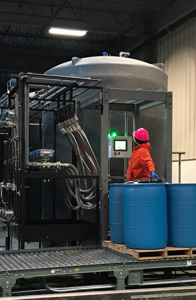 Tilley employee monitors the screen while the machine fills large blue barrels with product.