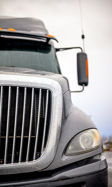 Upclose image of a commercial truck's front end.