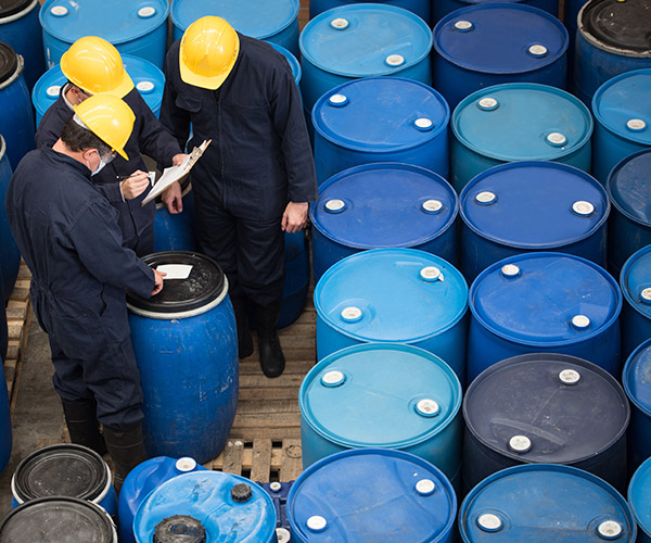 Men in hard hats studying clipboard, surrounded by blue industrial drums.