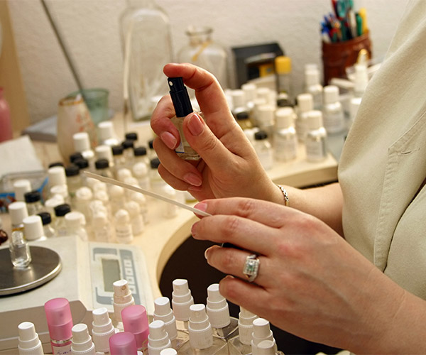 Upclose shot of woman's hands spraying perfume fragrances.