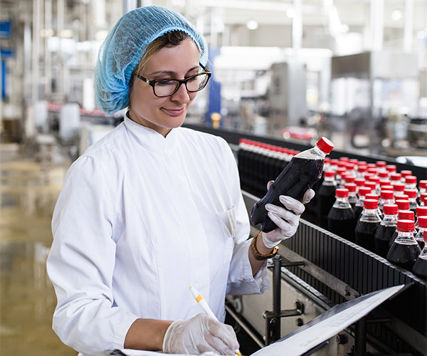 Woman inspecting beverages coming off production line.