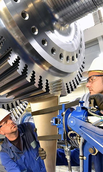 Workers assembling gas turbines in a factory.