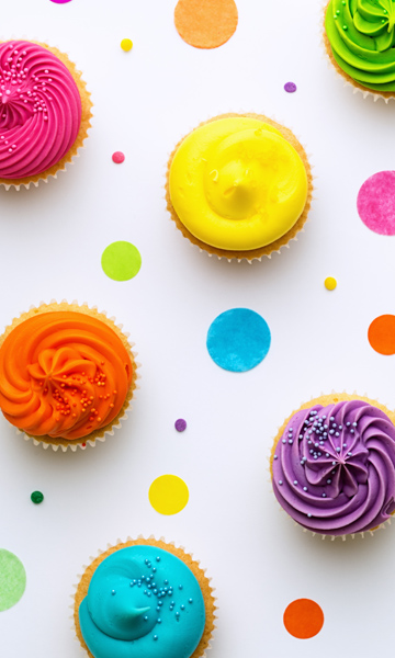 Oberhead shot of table with confetti and neon frosting on cupcakes.