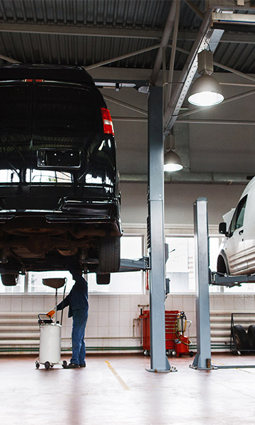 Two vehicles on lifts in a repair shop.