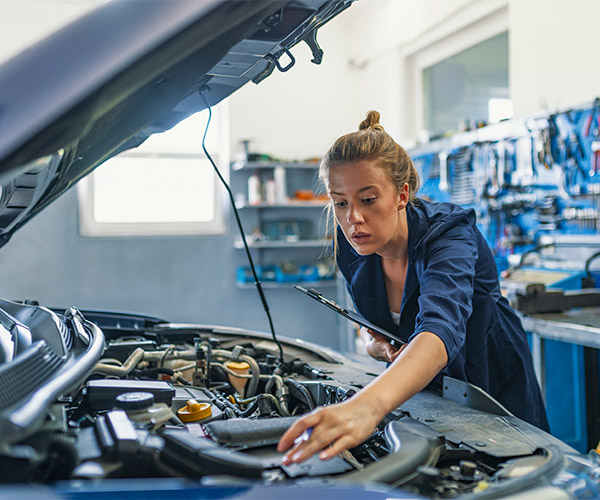 Female mechanic making notes about what's under a car's hood.