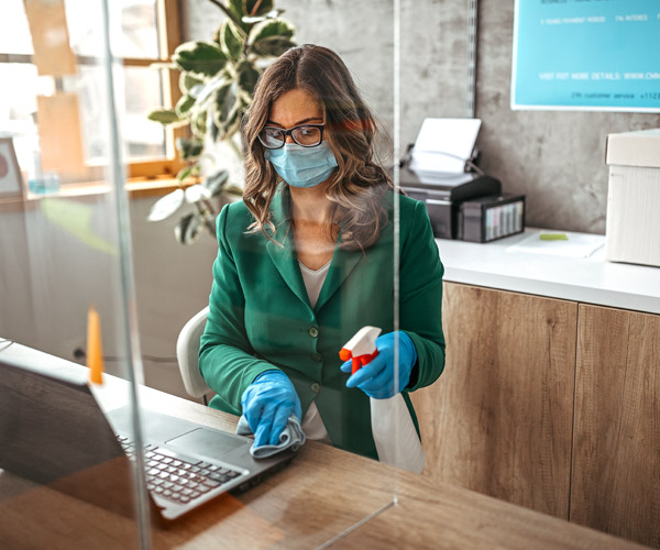 Masked professional woman sanitizing surfaces in her office.