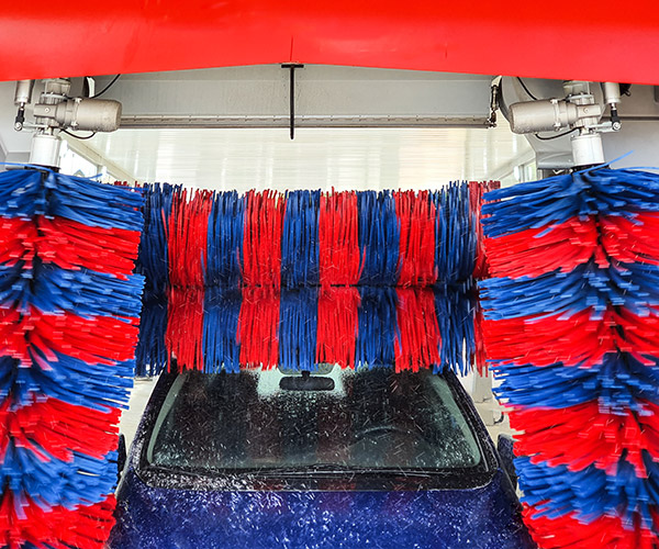 Car in car wash going through large brushes.