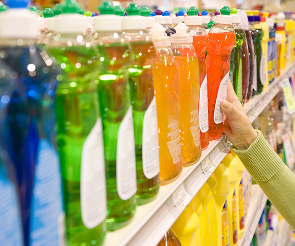 Choosing dish detergent on a supermarket shelf.