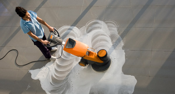 Woman cleaning the floor of an office building.