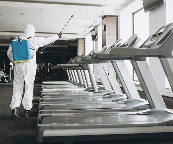 Spray cleaning the treadmills at a gym.