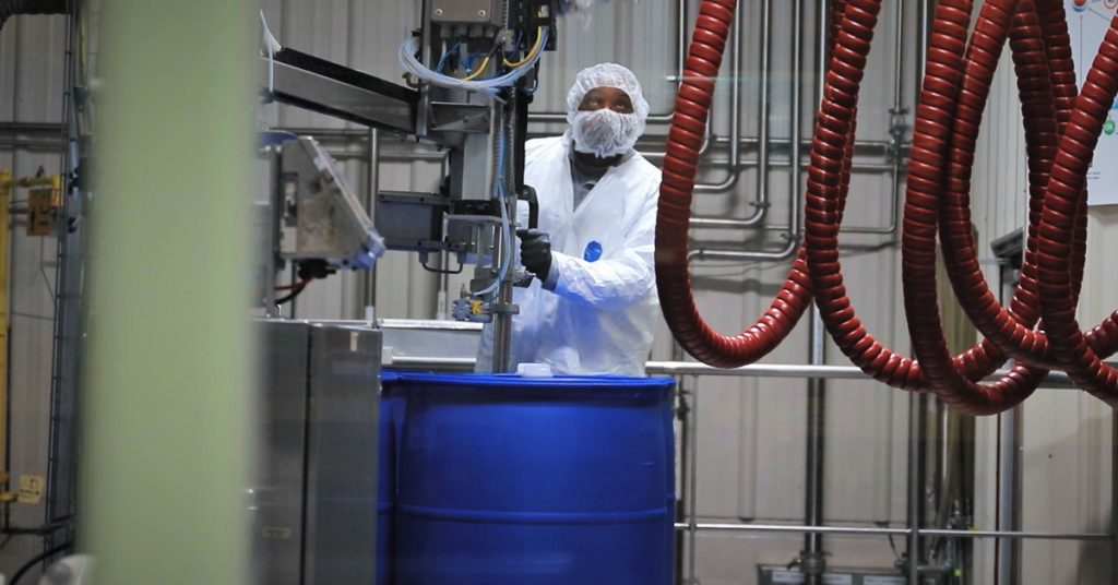 A Tilley Company employee fills a blue drum in the company's chemical distribution facility in Maryland.